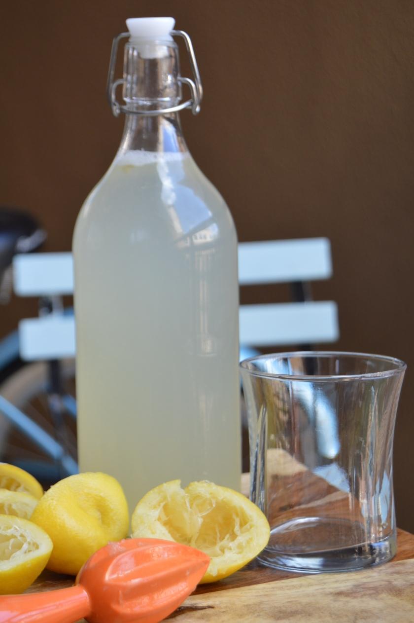 bottle of lemon water with lemons on cutting board